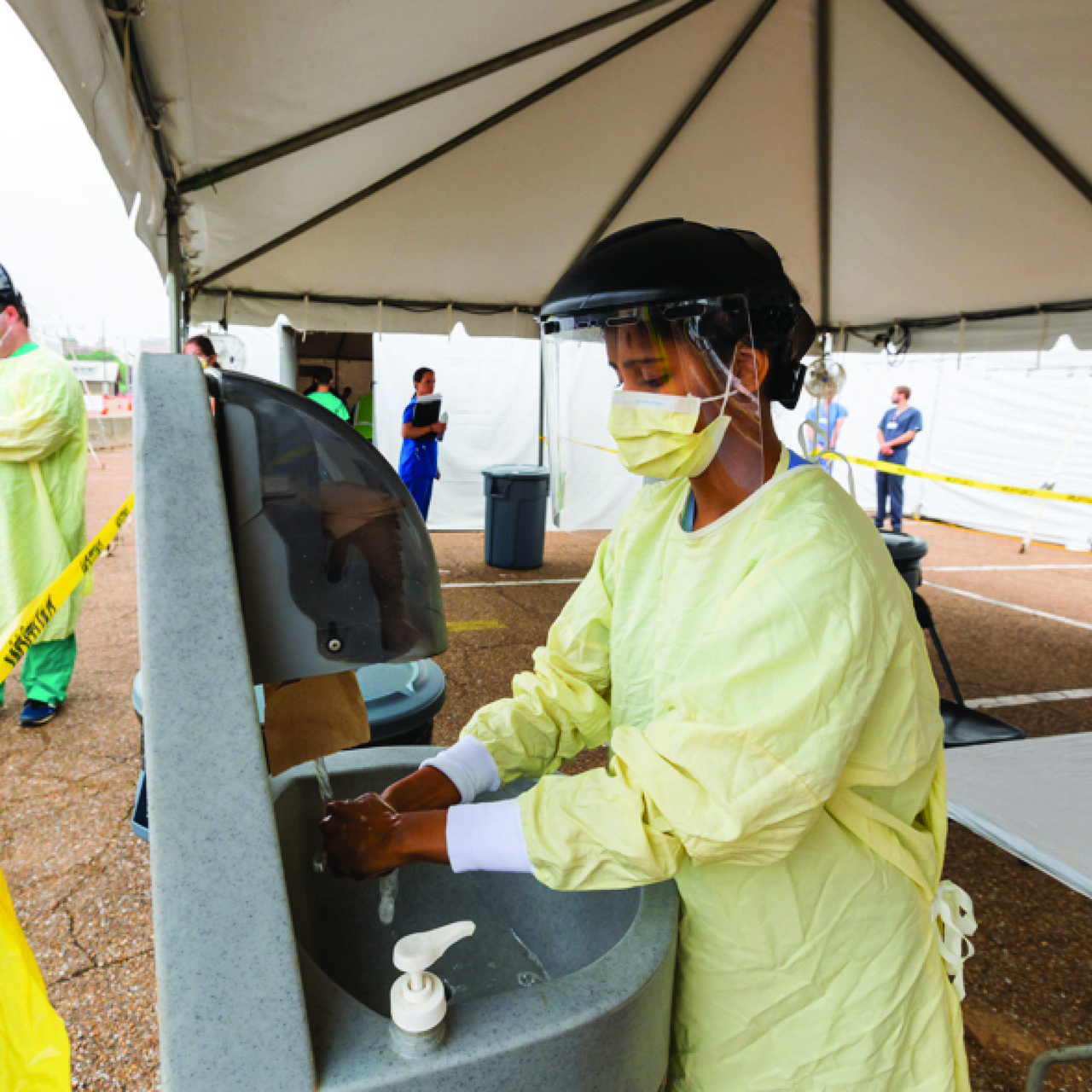 Medical professional washing hands in outdoor setting in fully protective gear