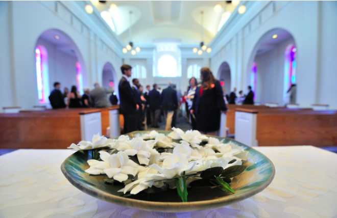 Gardenias In the Chapel in a bowl, and people gathered in pews