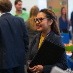 A smiling young lady in business attire attending a University of Mississippi job fair