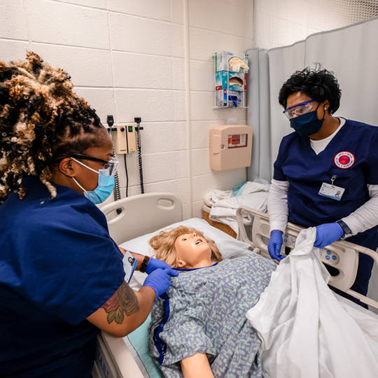 Nursing students wearing masks practicing in a hospital setting with a manikin patient.