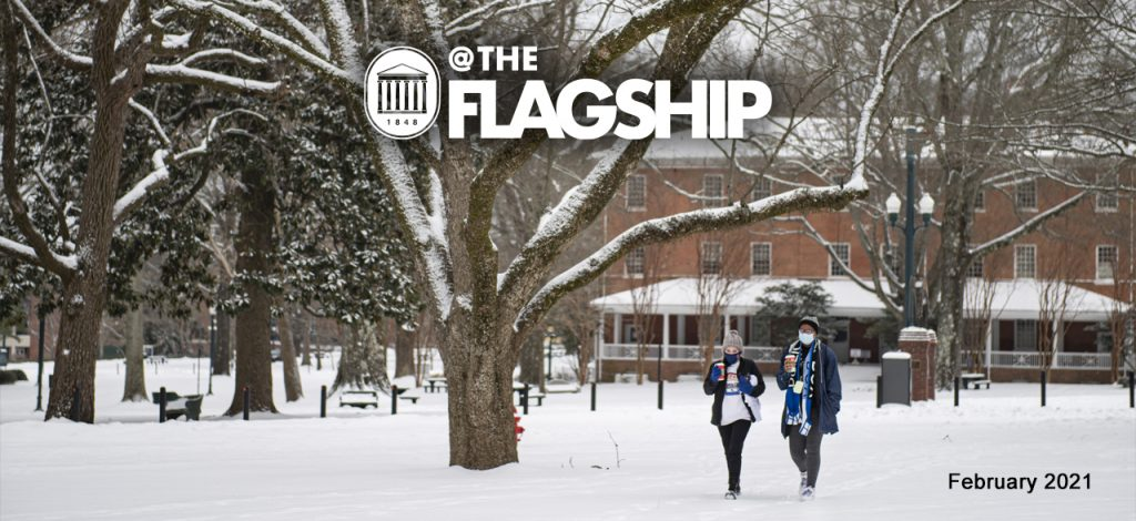 UM Crest, @The Flagship, February 2021, a couple of students bundled against the cold walk through the snow on campus