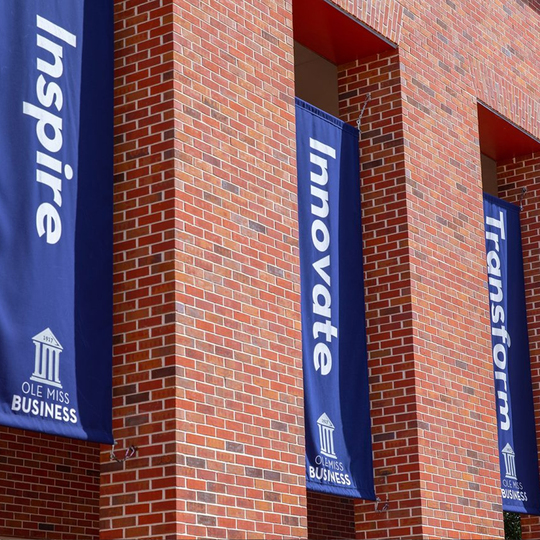 Brick Business School building on campus with blue banners that say Inspire, Innovate, and Transform.