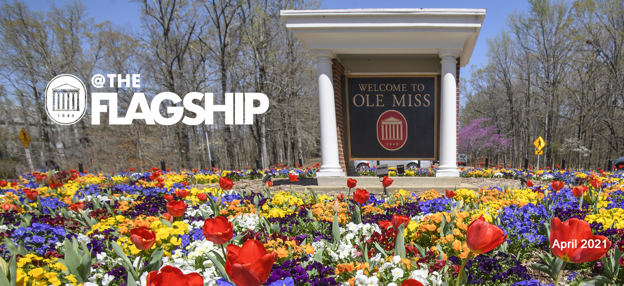 Flowers blooming at the entrance saying Welcome to Ole Miss, At the Flagship