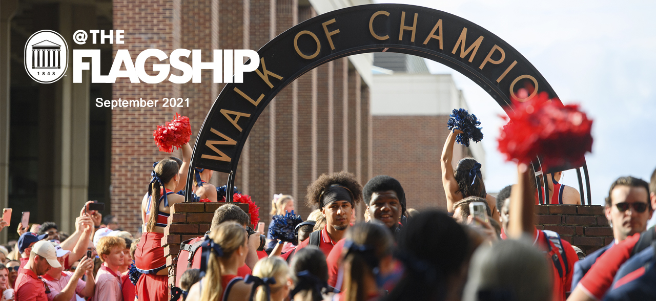 UM Crest, @The Flagship, September 2021, Ole Miss football players pass beneath the Walk of Champions arch as cheerleaders and fans cheer them on
