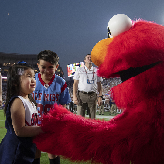 Ole Miss Wish Kid shaking hands with Elmo in the stadium