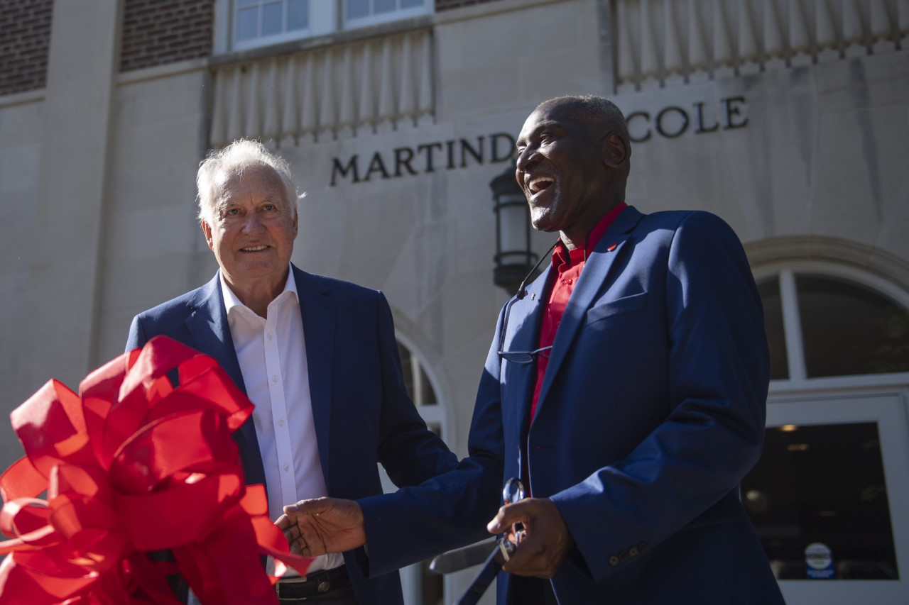 Martindale and Cole cutting the red ribbon in front of the Martindale-Cole building